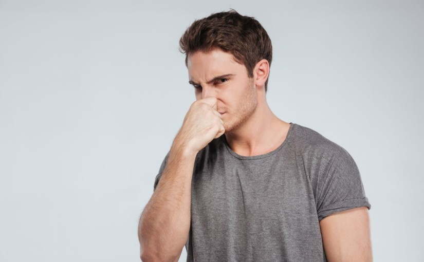 Portrait of a casual man covering his nose with hand
